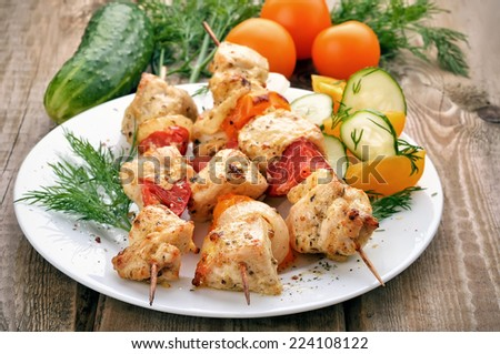 Chicken shish kebab on white plate and fresh vegetables on wooden table - stock photo