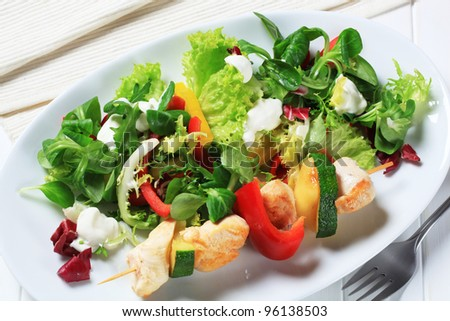 Chicken skewer with mixed salad greens  - stock photo