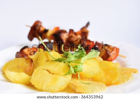 Chicken skewer with potatoes and arugula. Insulated food on a clean white background. - stock photo