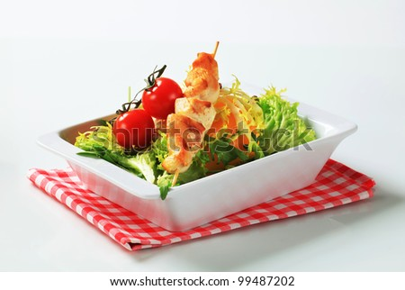 Chicken skewers and mixed salad greens  - stock photo