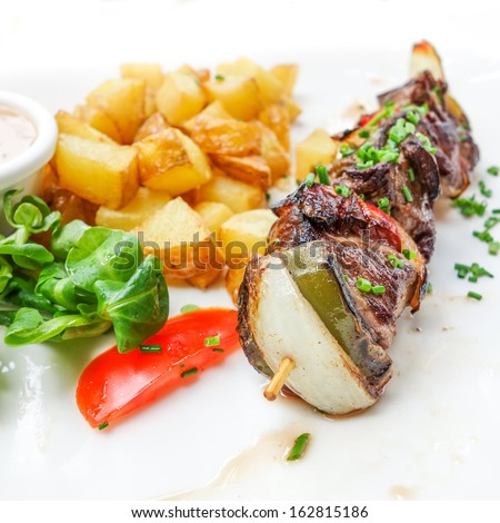 Chicken skewers with sauce and golden French fries potatoes
