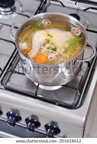 chicken soup being cooked on a gas stove - stock photo