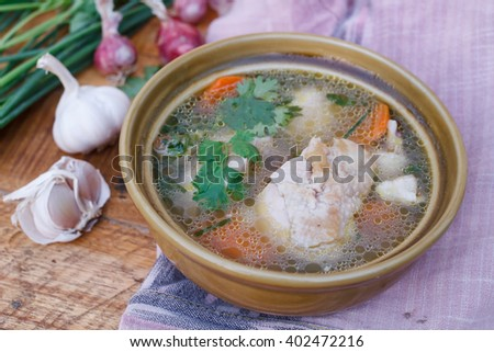 Chicken soup on wooden background.