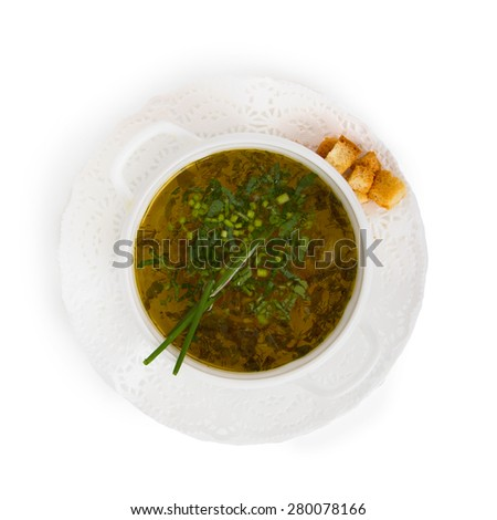 Chicken soup with chives and croutons in white plate. Isolated on white.