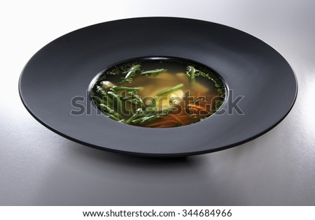 Chicken soup with eggs, carrot and asparagus seasoned with fresh parsley in black plate isolated on white