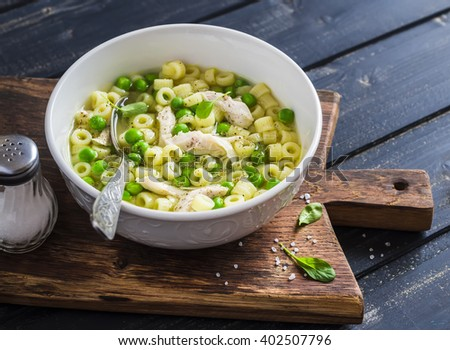 Chicken soup with pasta and green peas on a dark wooden board. Delicious healthy food - stock photo