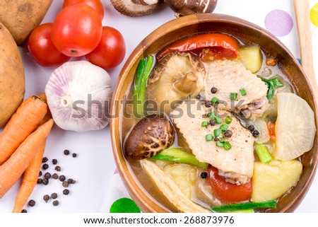 chicken soup with vegetables on table - stock photo