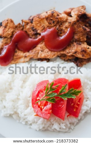 Chicken steak in a dish served with rice and vegetable. Vertical photo