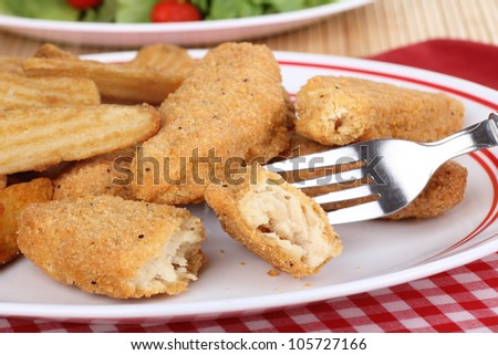 Chicken strip and fries meal with a piece on a fork