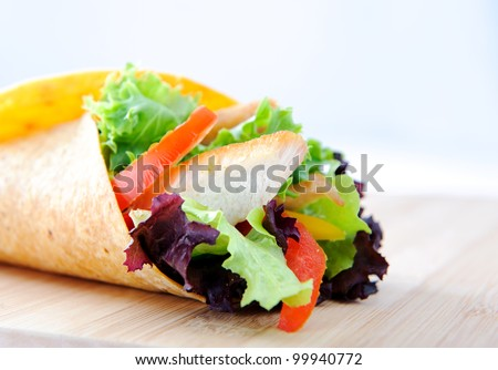 Chicken strips with fresh salad, bell peppers and tomato slices wrapped in a tortilla - stock photo