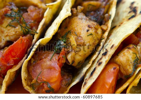 chicken tacos full with tomato and herbs on a yellow plate - stock photo