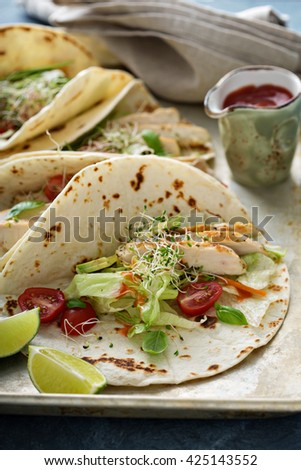 Chicken tacos with salad leaves and tomatoes