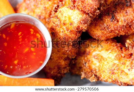 chicken tenders or strips with a spicy chilli sauce and vegetable sticks - stock photo