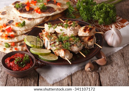Chicken tikka on skewers, naan flat bread and chutney closeup. horizontal