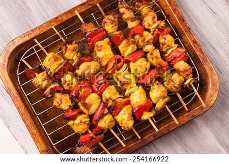 Chicken tikka on wooden sticks - stock photo