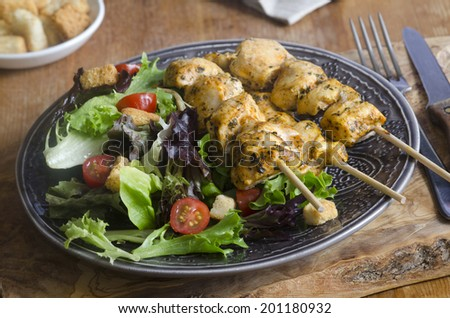 Chicken tikka skewers with leaf salad and croutons - stock photo