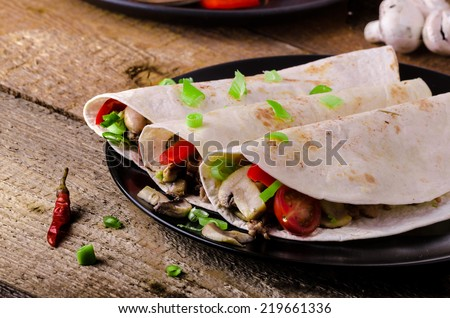 Chicken tortilla with mushrooms, garlic and spring onions - stock photo