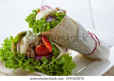 Chicken tortilla wrapped in special recyclable paper - stock photo