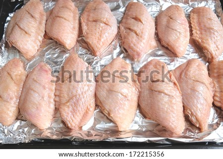 Chicken wing marinated with soy sauce on aluminium foil prepared for roast - stock photo