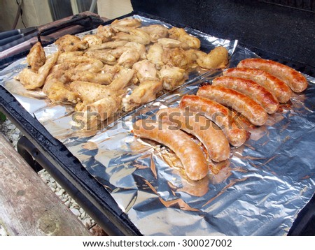 chicken wings and sausage being cooked on a smoker grill - stock photo
