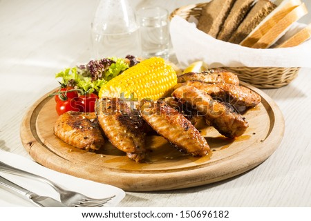 chicken wings are grilled on a wooden platter