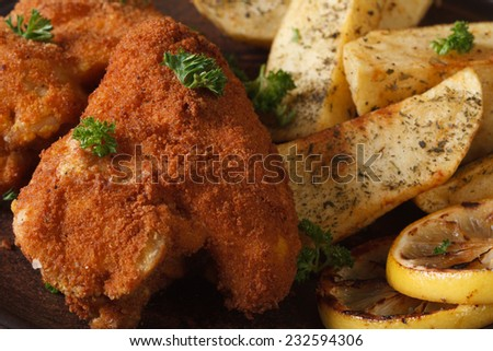 chicken wings dipped in batter macro with potatoes and lemon horizontal  - stock photo
