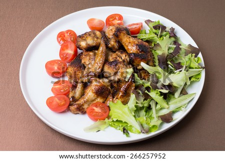 Chicken wings fried with honey decorated tomatoes and salad leaves on white ceramic plate on the brown background.