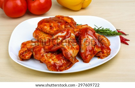 Chicken wings in red tomato sauce with rosemary - stock photo