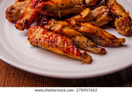 Chicken Wings, Oven Baked and Grilled. Homemade Tasty Food. Wood Table Background, Rustic Still Life Style. Close up. - stock photo