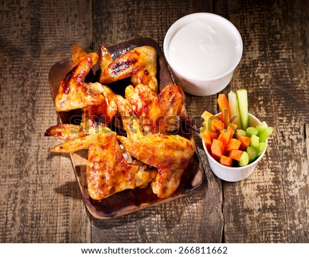 chicken wings with fresh vegetables and sauce on wooden table - stock photo
