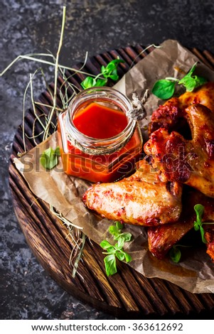 Chicken wings with hot tomato sauce on a chopping board. Grey stone background. Selective focus. - stock photo