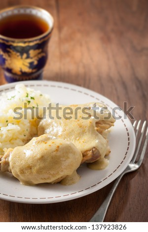 Chicken with curry sauce and rice on a dish with a tea cup on wooden table - stock photo