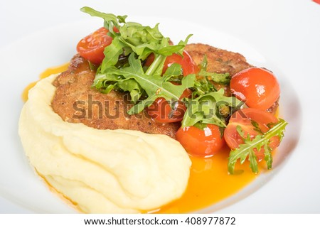 chicken with mashed potatoes and salad on a plate in a restaurant - stock photo