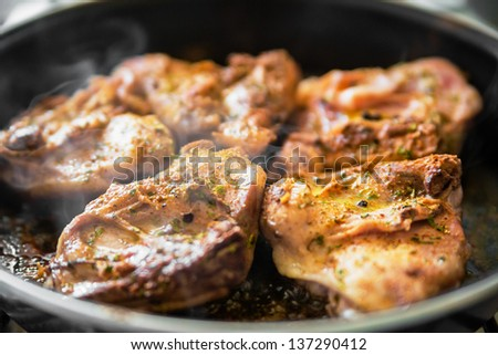 Chicken with spice on frying pan - stock photo