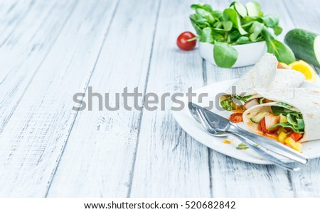 Chicken Wraps on a wooden table as detailed close-up shot (selective focus)