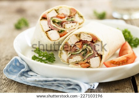Chicken wraps with pesto and bacon - stock photo