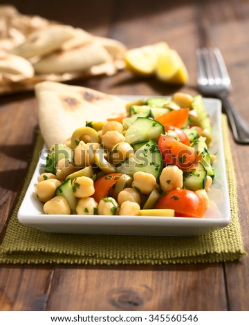 Chickpea salad with green olives, cucumber, cherry tomato and parsley, served on plate with pita bread pieces in back, photographed with natural light (Selective Focus, Focus one third into the salad) - stock photo