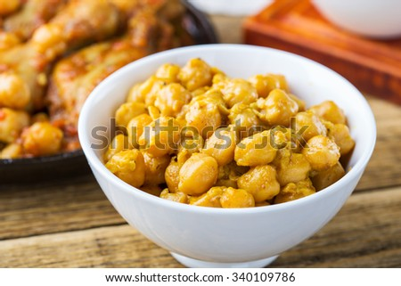 Chickpeas and chicken drumsticks curry  in frying pan on wooden table