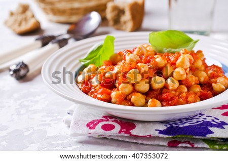 Chickpeas cooked with vegetable sauce. Selective focus. - stock photo