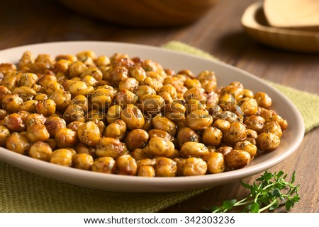 Chickpeas roasted with thyme, oregano, salt and pepper, photographed with natural light (Selective Focus, Focus in the middle of the chickpeas)