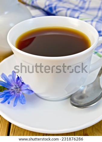 Chicory drink in a white cup with a flower on a saucer and spoon, napkin, milk jug on a wooden boards background - stock photo