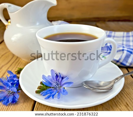 Chicory drink in a white cup with a flower on a saucer and spoon, napkin, milk jug on a wooden board - stock photo