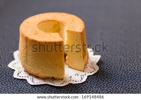 Chiffon cake on a paper doily - stock photo