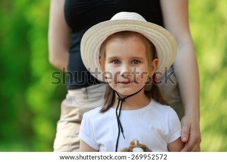 Child, a small little girl in yellow hat looking into the camera. Blurred background. Shallow depth of field. Focus on the model's face. - stock photo