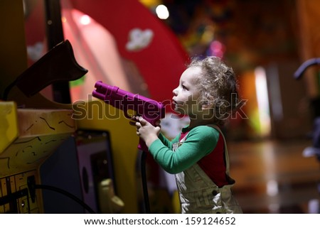 Child aiming a gun at indoor playground - stock photo