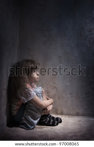 child alone in a dark corner - stock photo