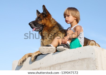 Child and a dog sitting on a concrete block. - stock photo