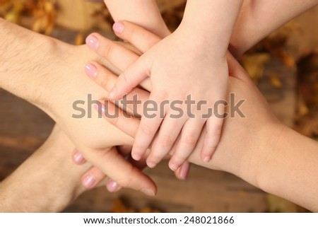 Child and father hands on wooden background