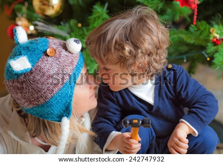 Child and his mam close to a Christmas tree - stock photo