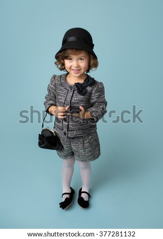 Child and kids fashion and clothing: girl in modern outfit on blue background - stock photo